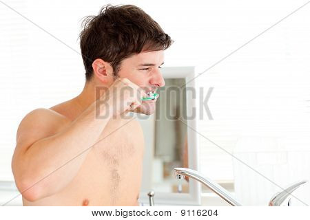 Handsome Young Man Brushing His Teeth In The Bathroom