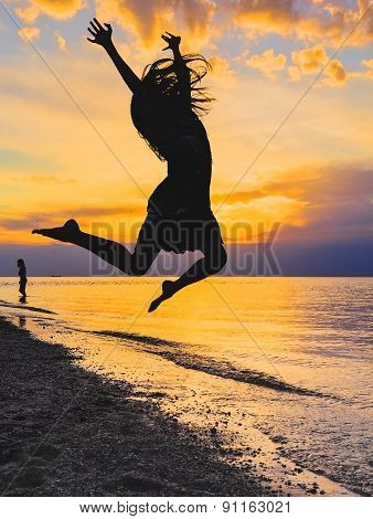 Silhouette Of A Girl Jumping At Sunset