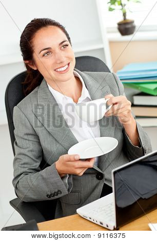 Businesswoman Holding A Cup Of Coffee In Front Of Her Laptop Sitting At Her Desk