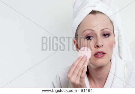 Woman Powdering Her Cheek With White Space For Copy
