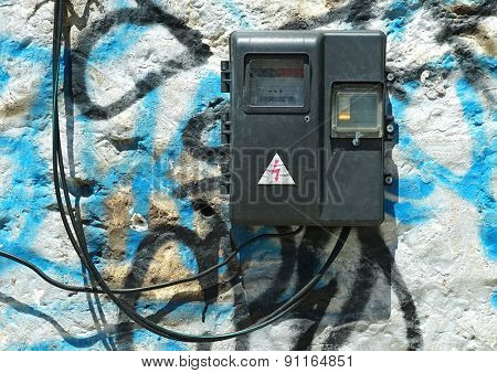 Old electric meter with wires on the painted stone wall.
