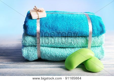 Still life with set of tied towels on wooden surface and light colorful background