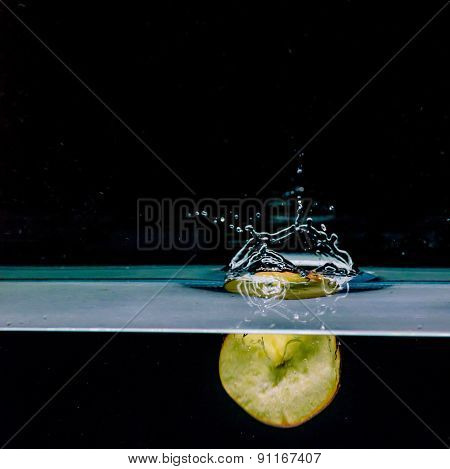 Red Apple Splashing Into Water, Isolated On Black Background