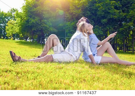 Relaxing Caucasian Couple Sitting Outdoors Together. Listening To Music In Headphones