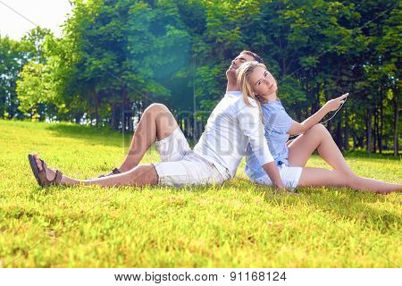 Relaxing Caucasian Couple Sitting Outdoors Together. Listening To Music
