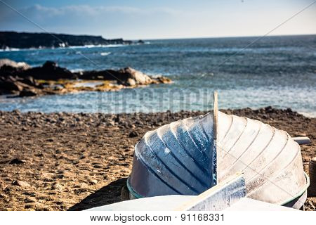 upturned boat on a sandy shore on sea background