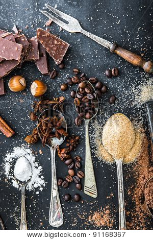 Sweet powdered ingredients in a spoon and chocolate on a table black