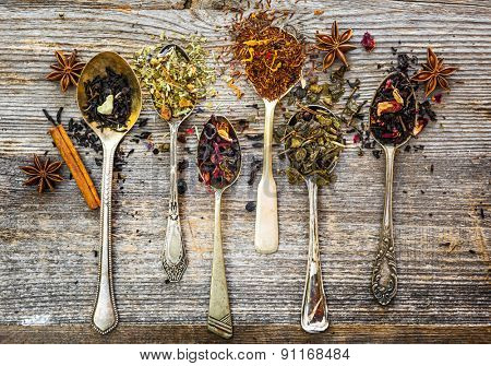 assortment of dry teas in silver spoons on wooden background