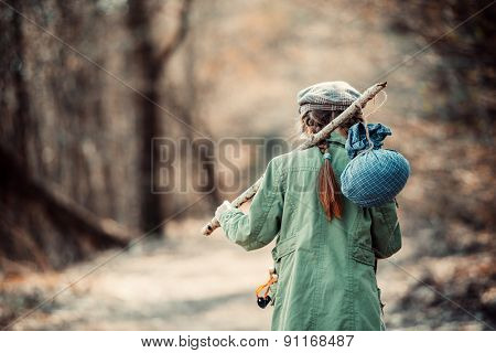 little girl goes on a footpath in the forest with stuff, photo in retro style