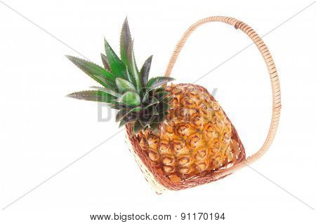 exotic fruit - single fresh raw pineapple in basket isolated over white background