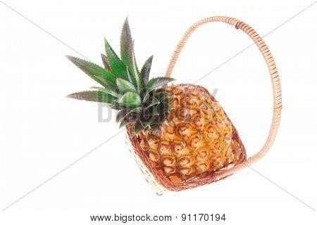 exotic fruit - single fresh raw pineapple in basket isolated over white background