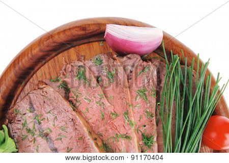 grilled beef slice on wooden plate over white
