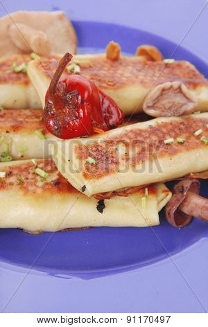 russian food - meat wrapped in a pancake with red hot pepper  and pickled mushrooms served on blue plate isolated over white background