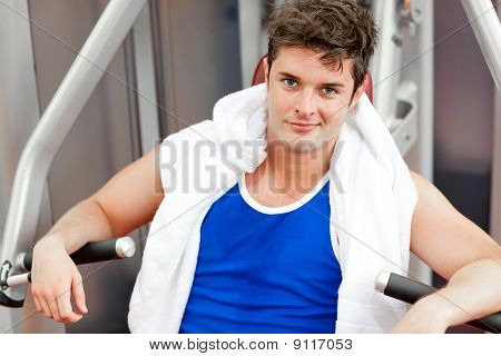 Confident Young Man With A Towel Using A Bench Press