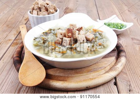 diet food : hot vegetable soup with bread  crackers in white bowl on wood stand over table
