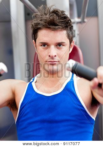 Confident Young Man Using A Bench Press