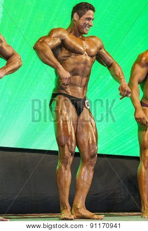 Professional Smiling Male Caucasian Bodybuilder Performing On Stage.