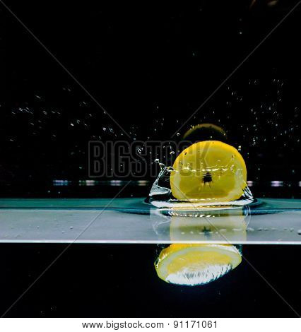 Lemon Into Water, Isolated On Black Background