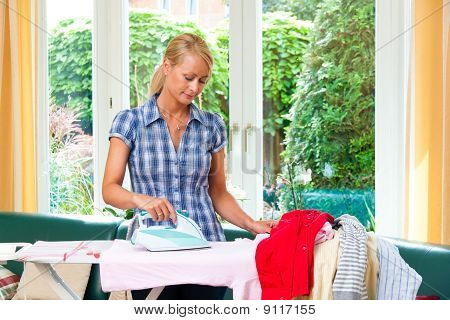 Housewife With Iron During Ironing And Laundry.