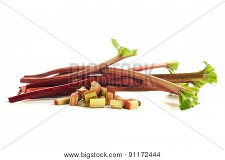 Whole and chopped stalks of rhubarb isolated on white background