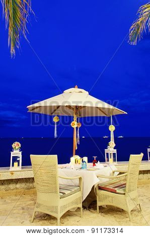 Romantic table set up dinner on the beach, twilight time