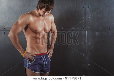 Portrait of fit athletic muscular shirtless young man looking down Fitness sport training lifestyle