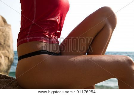 Sexy Girl In Sportswear And Tanga String Sitting On The Cliff Of The Rocky Beach .