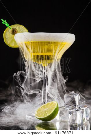 Martini drink with dry ice smoke effect, served on glass table with black background