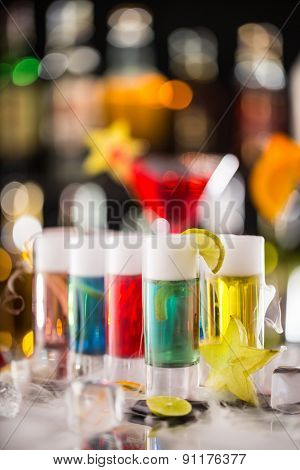 Variation of hard alcoholic shots with dry ice smoke effect, served on bar counter. Blur bottles on background