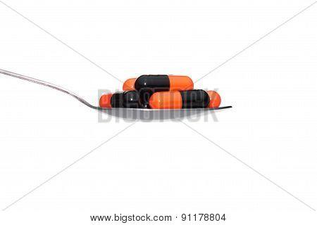 Black Orange Medicine Or Capsule On Spoon Isolated On White Background