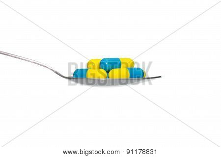 Blue Yellow Medicine Or Capsule On Spoon Isolated On White Background