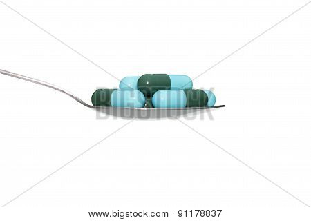 Green Blue Medicine Or Capsule On Spoon Isolated On White Background