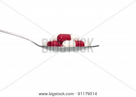 Red White Medicine Or Capsule On Spoon Isolated On White Background