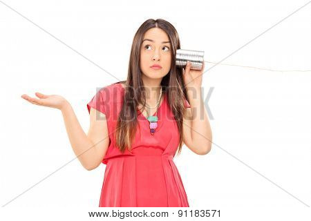 Young confused woman talking through a tin can phone and gesturing with her hand isolated on white background
