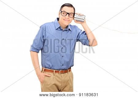 Cheerful young man talking through a tin can phone isolated on white background