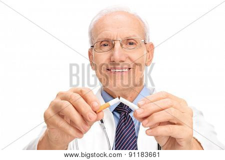 Mature doctor breaking a cigarette in half and looking at the camera isolated on white background