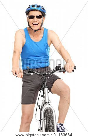 Vertical shot of a joyful senior cyclist sitting on his bike and looking at the camera isolated on white background