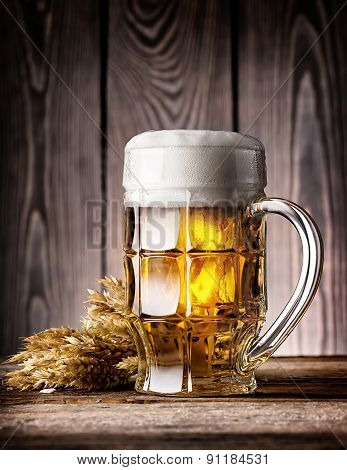 Faceted mug of light beer with foam and ears