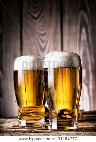 Two glasses of light beer with foam