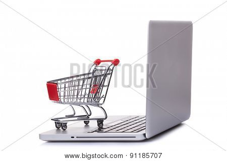 Shopping cart on laptop computer, isolated on white background