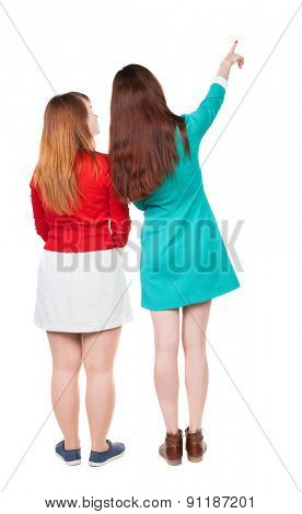 Back view of two pointing young girl. Rear view people collection.  backside view of person. . Rear view. Isolated over white background. Two young girls are considering something on the top right.