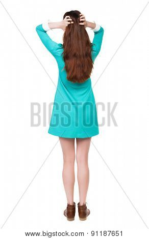 Back view of shocked woman in dress. upset young girl.   backside view of person.  Isolated over white background. The girl in a blue dress with brown shoes straightens her hair with his hands.