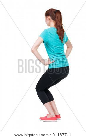 slim girl in sportswear is engaged in sports. She squats. Rear view people collection.  backside view of person.  Isolated over white background. She bent her knees doing exercises