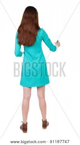 back view of writing beautiful woman. Rear view people collection.  backside view of person. Isolated over white background.  girl in blue dress with brown shoes draws felt-tip pen with his right hand