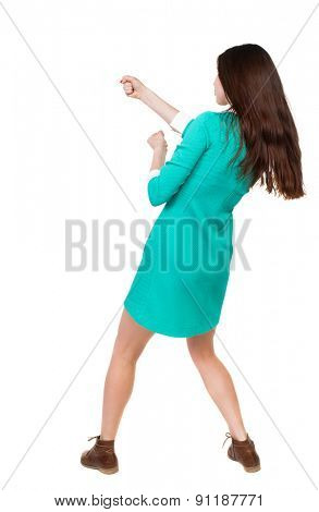 back view of standing woman pulling a rope from top or cling to something.  Rear view people collection.  Isolated over white background. girl in a green dress simply pulls the top left something