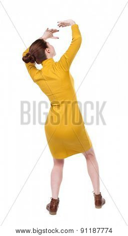 back view woman protects hands from what is falling from above. Rear view people collection. backside view person. Girl in mustard strict dress crouching hands protected from incident from sky