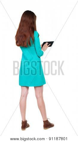 back view of standing young beautiful  girl with tablet computer in the hands of. girl  watching. Rear view people collection.  The girl in a blue dress with brown shoes running on a Tablet PC