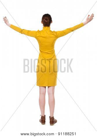 Back view of Beautiful woman in dress looking at wall and Holds  hand up.  Rear view people. Isolated over white background.. Girl in mustard strict dress is turning palm to sky.