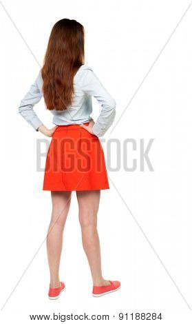 back view of standing young beautiful  woman in dress.  Rear view people collection.  backside view of person.  Isolated over white background. A woman in a red skirt standing with hands on hips.