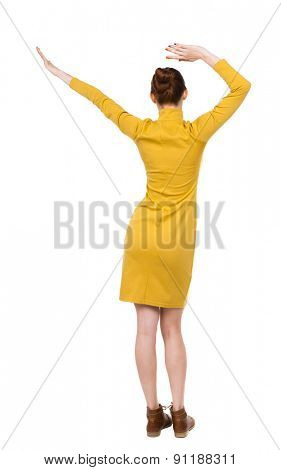 back view of dancing young beautiful  woman in dress. Rear view people collection.  backside view of person.  Isolated over white background. Girl in mustard strict dress dancing with his hands raised